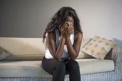 在家坐沮丧的沙发长沙发感觉急切和沮丧的sufferi的年轻可爱和哀伤的黑人非裔美国人的妇女 免版税库存图片