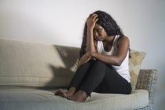 在家坐沮丧的沙发长沙发的年轻可爱和哀伤的黑人非裔美国人的妇女感觉急切和沮丧的sufferin 免版税库存照片