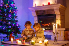 在家坐由壁炉的两个小孩在圣诞节 免版税库存图片