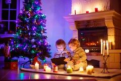 在家坐由壁炉的两个小孩在圣诞节 免版税图库摄影