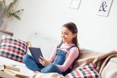 在家坐看书微笑的女孩快乐 免版税库存图片