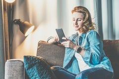 在家坐长沙发和使用智能手机的牛仔布衬衣的年轻微笑的妇女 女孩使用数字式小配件 免版税图库摄影