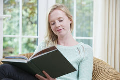 在家坐阅读书的十几岁的女孩 图库摄影