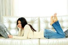 在家基于有片剂计算机的一个沙发的愉快的妇女 免版税图库摄影