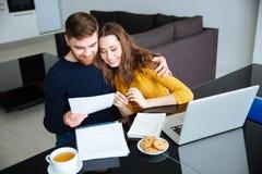 在家处理他们的票据的夫妇 免版税图库摄影