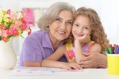 在家学习与祖母的女小学生画象 库存照片