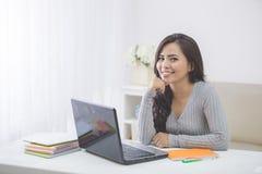 在家学习使用膝上型计算机的亚裔女学生 库存照片