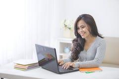 在家学习使用膝上型计算机的亚裔女学生 免版税库存照片