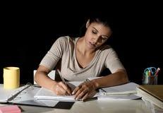 在家学习在笔记薄的年轻繁忙的美丽的西班牙女孩夜间看起来的准备的检查文字 图库摄影