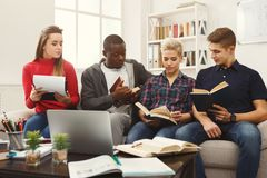 在家学习在长沙发的小组不同的学生大气 免版税库存图片
