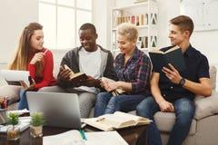 在家学习在长沙发的小组不同的学生大气 库存照片