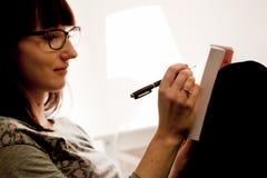 在家学习坐床和采取的一个少妇在书的笔记。 免版税库存图片