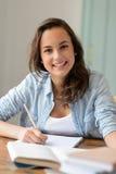 在家学习微笑的少年学生女孩 免版税库存照片