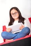 在家学会与片剂个人计算机的女小学生 免版税库存照片