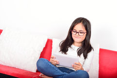 在家学会与片剂个人计算机的女小学生 免版税库存图片