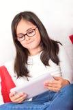 在家学会与片剂个人计算机的女小学生 库存图片