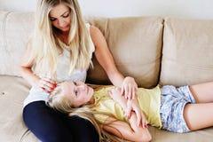 在家安慰她的十几岁的女儿的母亲 免版税库存照片