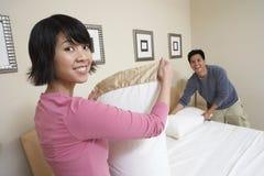 在家安排床的夫妇 免版税库存照片
