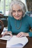 在家审阅票据的微笑的资深妇女 免版税图库摄影