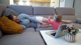 在家工作与一个婴孩的妇女母亲在计算机后通过互联网 影视素材
