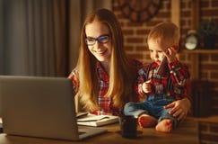 在家工作与一个婴孩的妇女母亲在计算机后 免版税库存图片