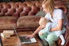 在家工作与女婴的年轻母亲 免版税库存图片