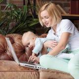 在家工作与女婴的年轻母亲 免版税库存照片