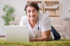 在家工作和听到音乐的自由职业者 库存照片