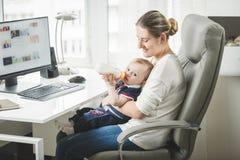 在家工作和照顾他的年轻自己经营的母亲 库存图片