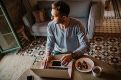 在家工作在客厅的英俊的工友人 使用膝上型计算机和手机,供以人员坐在木桌上 蠢材 库存图片