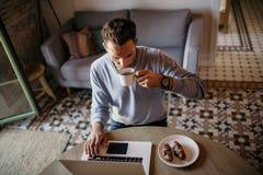 在家工作在客厅的英俊的工友人 使用膝上型计算机和手机,供以人员坐在木桌上 蠢材 图库摄影