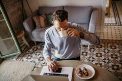 在家工作在客厅的英俊的工友人 使用膝上型计算机和手机,供以人员坐在木桌上 蠢材 库存照片