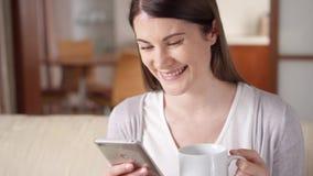 在家工作在手机的微笑的女实业家喝咖啡 家庭办公室概念 股票视频