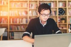 在家工作在膝上型计算机办公室或图书馆的年轻亚裔人有严肃的面孔的,书架有时钟迷离背景与时钟 图库摄影