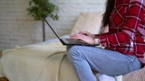 在家工作在膝上型计算机后的少妇 穿戴在格子花呢上衣,反对砖墙背景 股票录像