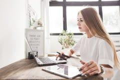 在家工作在膝上型计算机和片剂后的年轻女商人 创造性的斯堪的纳维亚样式工作区 免版税库存图片
