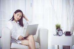 在家工作在膝上型计算机comouter的快乐的企业夫人 免版税库存照片