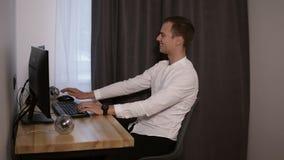 在家工作年轻人的自由职业者,在书桌,键入坐键盘,使用老鼠 放松的白色衬衣的人和 股票视频