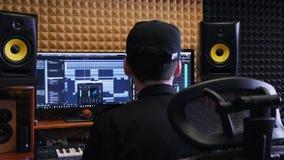 在家工作有显示器和调平器混合的齿轮的录音师音乐演播室在屏幕上 掌握音乐的工程师混合和 影视素材