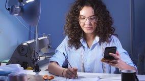 在家工作演播室的年轻创造性的女孩设计师在晚上 缝合的事务 影视素材