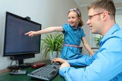 在家工作的父亲和的女儿 免版税库存图片