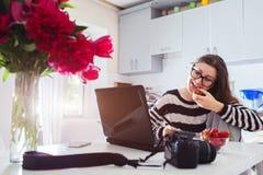 在家工作自由职业者的摄影师 使用照相机和笔片剂,妇女研究膝上型计算机 开始  免版税图库摄影