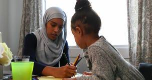 在家帮助她的有她的家庭作业的年轻母亲女儿在桌4k上 股票视频