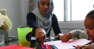在家帮助她的有家庭作业的年轻母亲女儿在桌4k上 影视素材