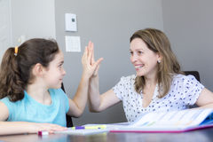 在家帮助她的有家庭作业的成熟母亲孩子 免版税库存图片