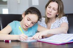 在家帮助她的有家庭作业的成熟母亲孩子 免版税图库摄影