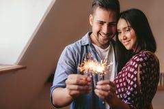 在家庆祝与闪烁发光物的爱恋的年轻夫妇 免版税库存图片