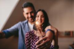 在家庆祝与闪烁发光物的年轻夫妇 免版税图库摄影