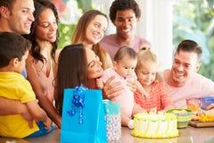 在家庆祝儿童的第一个生日的小组家庭 图库摄影