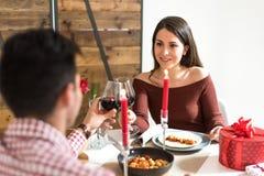 在家庆祝华伦泰与晚餐的年轻愉快的夫妇` s天敬酒用酒 免版税库存照片